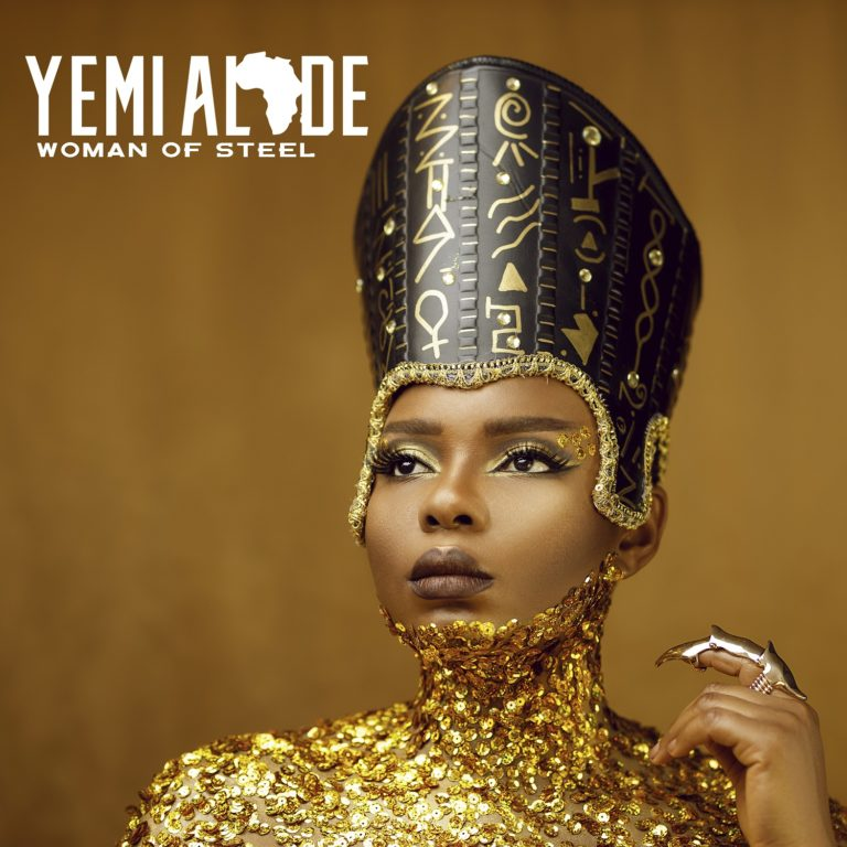 An image of Yemi Alade clad in an Egyptian headpiece and a black dress, complete with gold body glitter.